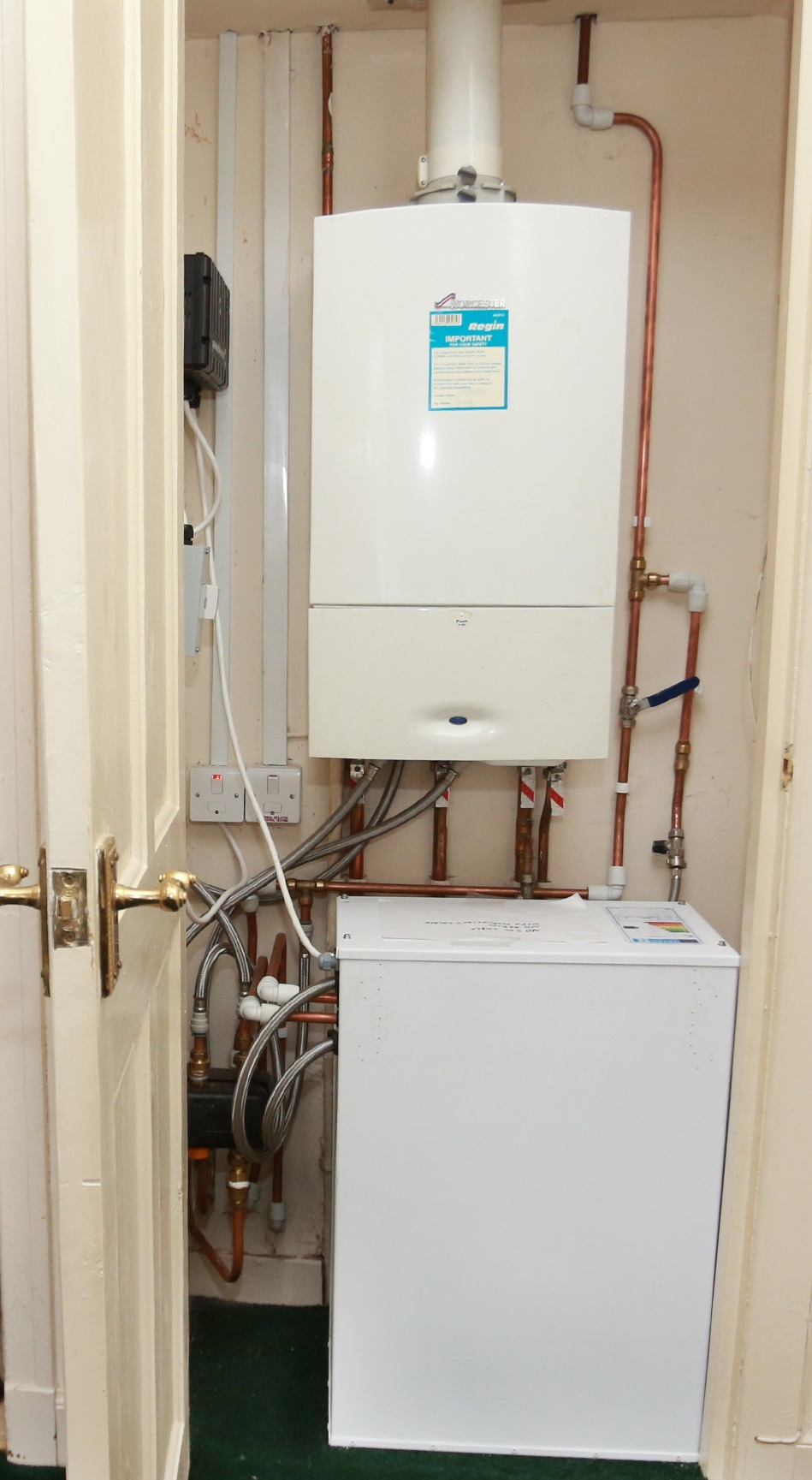 A Sunamp thermal battery inside a small cupboard below a gas boiler
